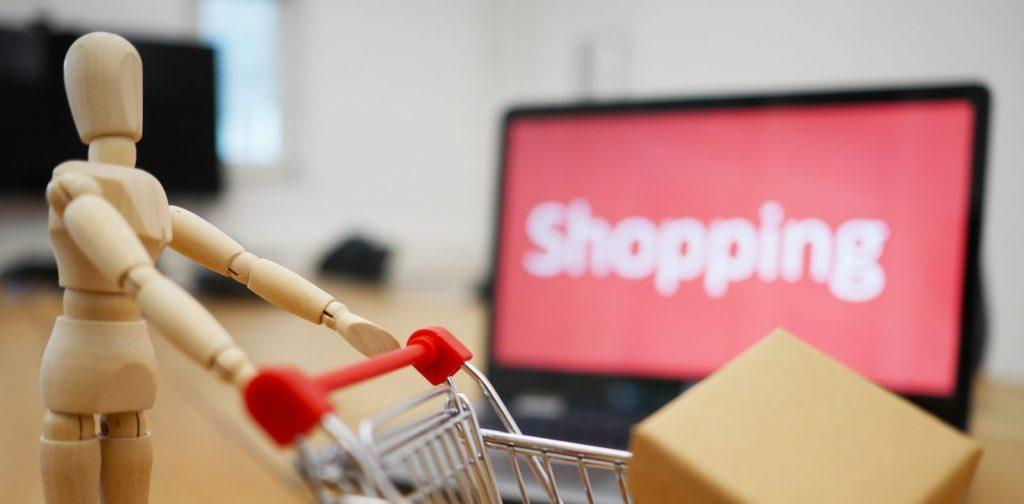 Muñeco de madera con un carrito de la compra, y una pantalla con la palabra 'shopping' al fondo