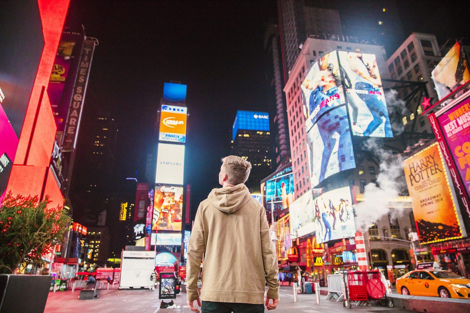 Una persona en Time Square contemplando una gran cantidad de anuncios